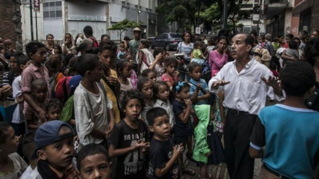 Niños esperan en un comedor.
