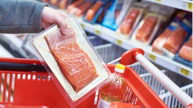 Imagem mostra mulher pondo um pacote de salmão em um carrinho de supermercado