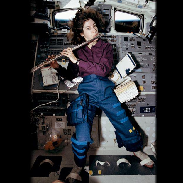 Ellen Ochoa tocando la flauta en el espacio.