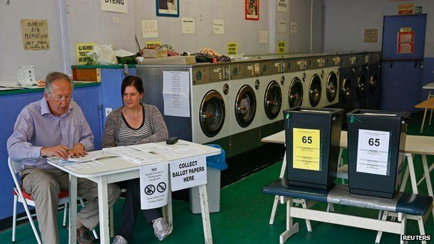 Poll clerks are seen in a public launderette being used as a polling station in Oxford, southern England
