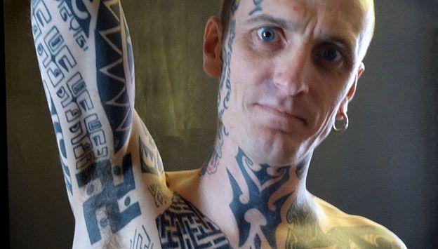 El hombre (Phil Cummins) que muestra esvástica tatuada