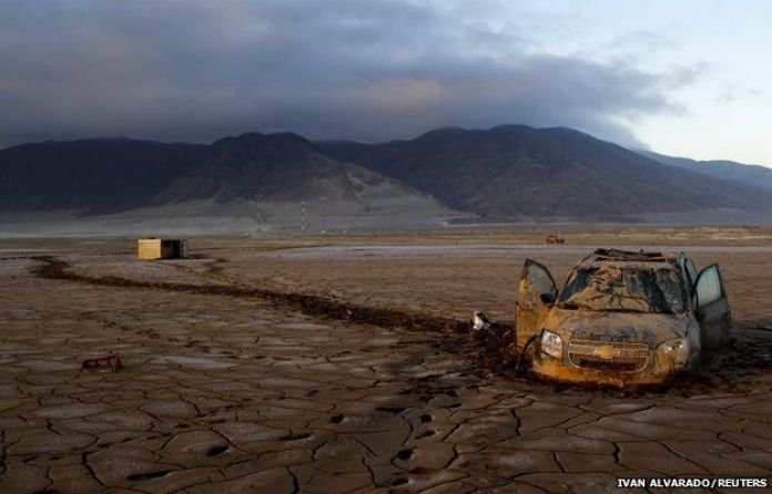 A vehicle partially submerged in dry mud is pictured in an area that was hit by floods at Chanaral town, Chile