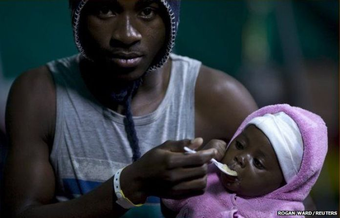 A man feeds his young child in Isipingo, south of Durban