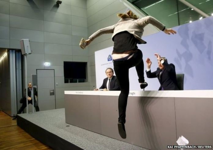 A protester jumps on the table in front of the European Central Bank President Mario Draghi