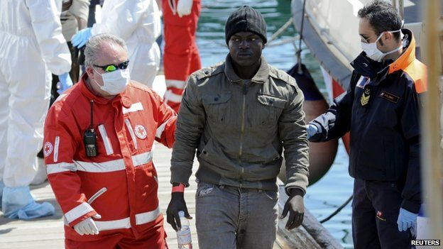 A migrant is helped as he disembarks from a Coast Guard boat in the Sicilian harbour of Palermo on 15 April 2015