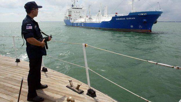 Estrecho de Malaca, con un barco y un oficial de policía en la orilla.