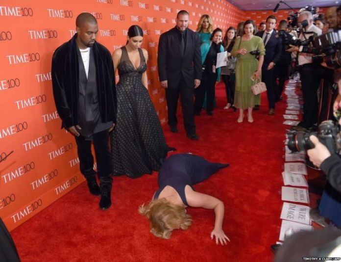 Comedian Amy Schumer pretends to trip and fall on the floor in front of Kim Kardashian (2nd-L) and Kanye West (L) as they attend the Time 100 Gala celebrating the Time 100 issue of the Most Influential People at The World at Jazz at Lincoln Center on April 21, 2015 in New York.