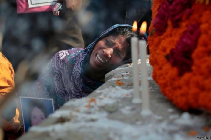 A Bangladeshi relative of a victim cries in front of a monument