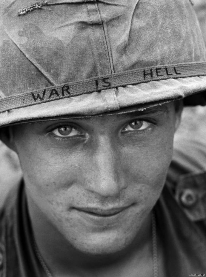 An unidentified American soldier wears a hand written slogan on his helmet in June 1965