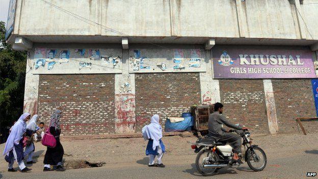 Pakistani female students walk past the school of child activist, Malala Yousafzai, in Mingora the capital of Swat Valley (23 Sept 2013)