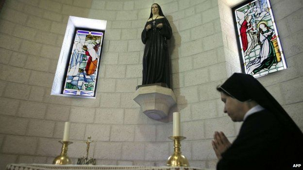 A sister prays in front of relics of Marie Alphonsine Ghattas at the Mamilla monastery in Jerusalem on May 12, 2015, a few days ahead of the canonisation of the Palestinian nun in Rome