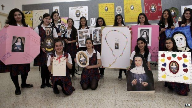 """Students of the Rosary Sisters girls"""" secondary school in Jerusalem""""s northern neighborhood of Beit Hanina pose with portraits of Sister Marie Alphonsine Ghattas, on May 12, 2015"""