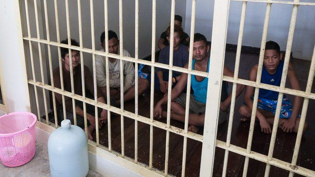 Migrant camp guards locked up in a police cell