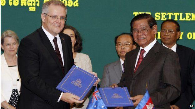 Australian Immigration Minister Scott Morrison, left, shows a signed document with Cambodian Interior Minister Sar Kheng in Phnom Penh (Sept 2014)