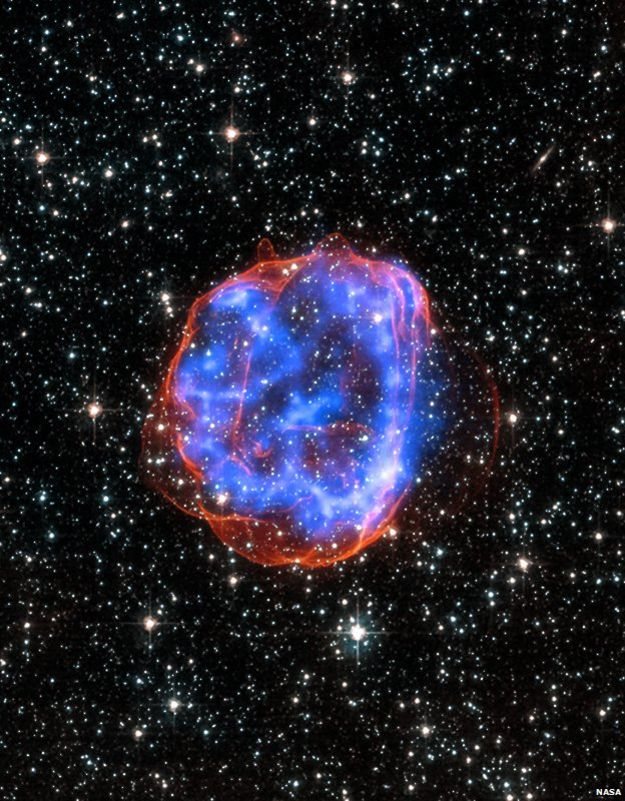 When a massive star exploded in the Large Magellanic Cloud, a satellite galaxy to the Milky Way, it left behind an expanding shell of debris called SNR 0519-69.0. Here, multimillion degree gas is seen in X-rays from Chandra (blue). The outer edge of the explosion (red) and stars in the field of view are seen in visible light from Hubble.