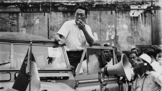 Singapore Prime Minister Lee Kuan Yew stands on the running board of a government vehicle in Singapore as he addressed a crowd in a slum area, in July 29, 1964. Yew, popular with the masses, asked for a halt in the racial strife that has struck the island city.