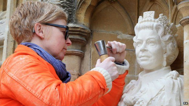 Sculptor Nina Bilbey puts the finishing touches to her statue of the Queen
