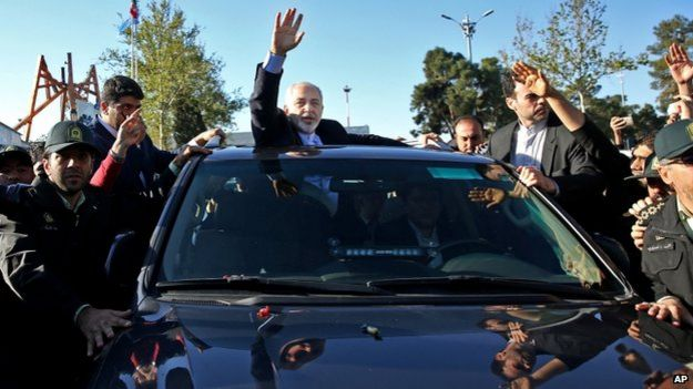 Iranian Foreign Minister Mohammad Javad Zarif, who is also Iran's top nuclear negotiator, waves to his well wishers upon arrival at the Mehrabad airport in Tehran, Iran