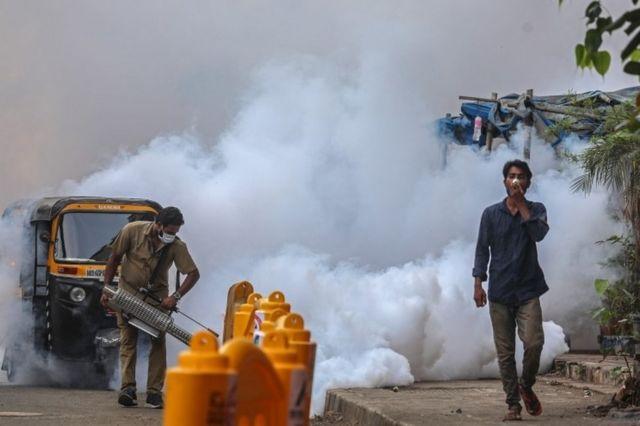 Um trabalhador municipal usando uma máscara facial usa máquina de spray de fumigação perto de um centro de vacinação em Mumbai, Índia, 30 de abril de 2021