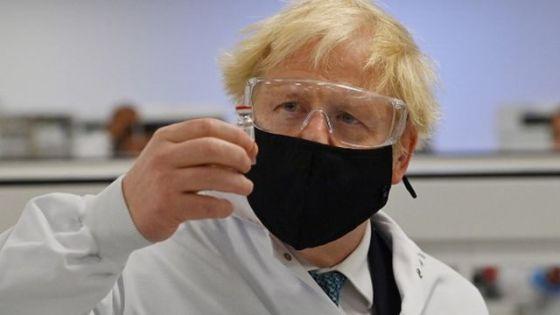Foto do primeiro-ministro Boris Johnson com máscara segurando um frasco de vacina