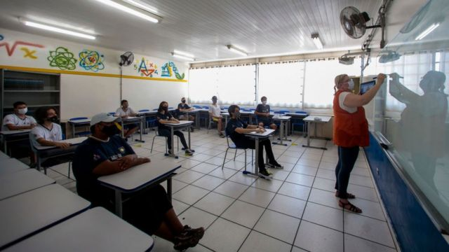Students attend a class and maintain preventive measures at a school in Sao Paulo, Brazil