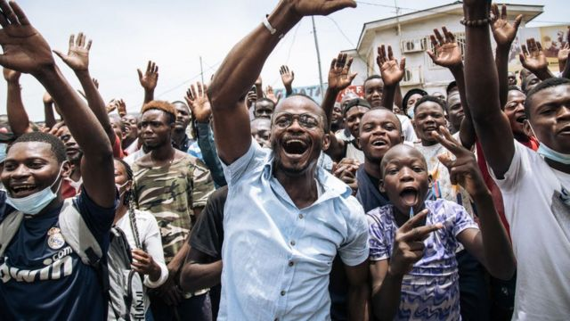 Supporters of the current Congolese president, Denis Sassou-Nguesso, wave to the president after he cast his vote in Brazzaville on March 21, 2021.