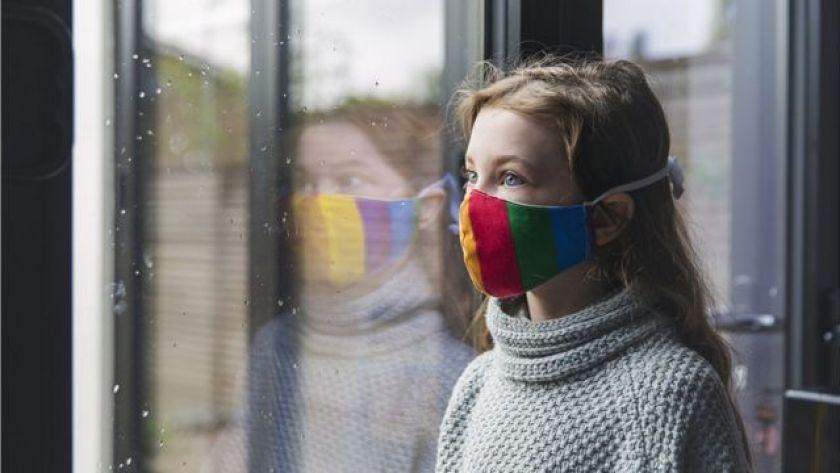 Girl wearing mask standing in a window