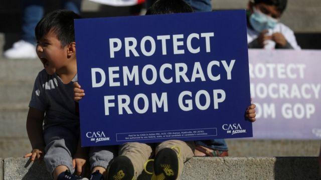 """Personas con carteles que dicen: """"protejan la democracia del Partido Republicano"""""""