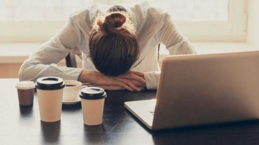 Mulher exausta na frente do computador