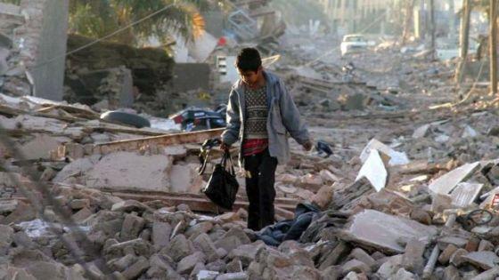 Menino caminha pelos escombros após o terremoto de 2003 em Bam, Irã.