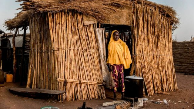Woman standing in front of a thatched hut