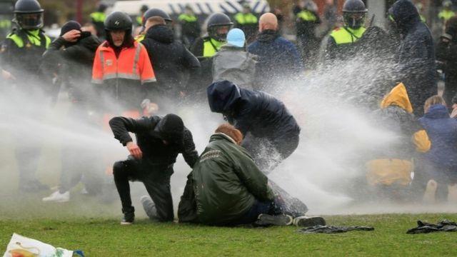 La policía usa un chorro de agua a presión contra los manifestantes en Amsterdam.