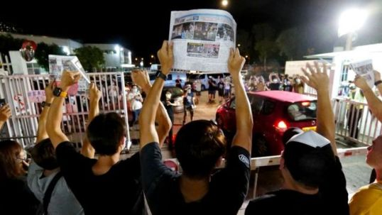 Apple Daily journalists hold freshly-printed copies of the newspaper's last edition while acknowledging supporters gathered outside their office in Hong Kong