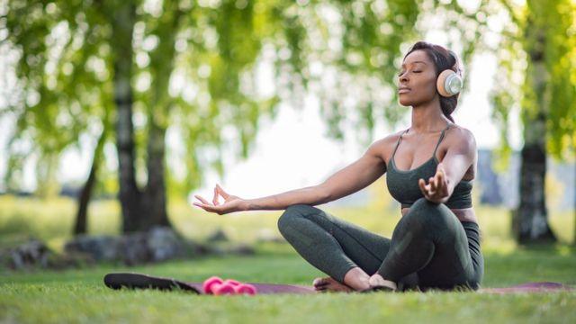 Mulher meditando em área verde