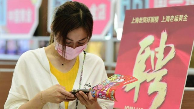 A woman checking information on her phone during a job fair in Hai'an City, Jiangsu Province, China, in May 2020