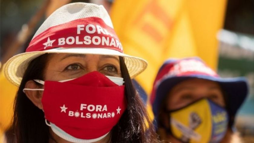 Woman wearing mask and hat with PT symbol and phrase 'Fora Bolsonaro'