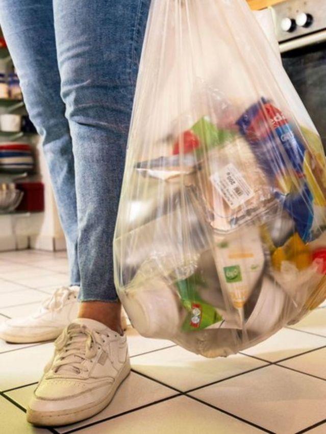 Mulher segurando sacola com lixo plástico