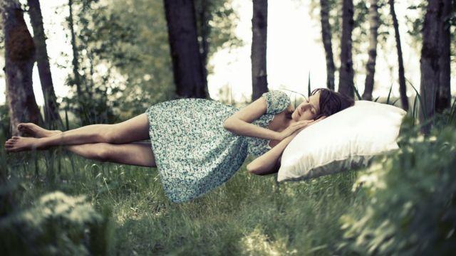 femme endormie, flottant sur une forêt
