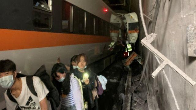 人们沿着花莲以北隧道中脱轨的火车走