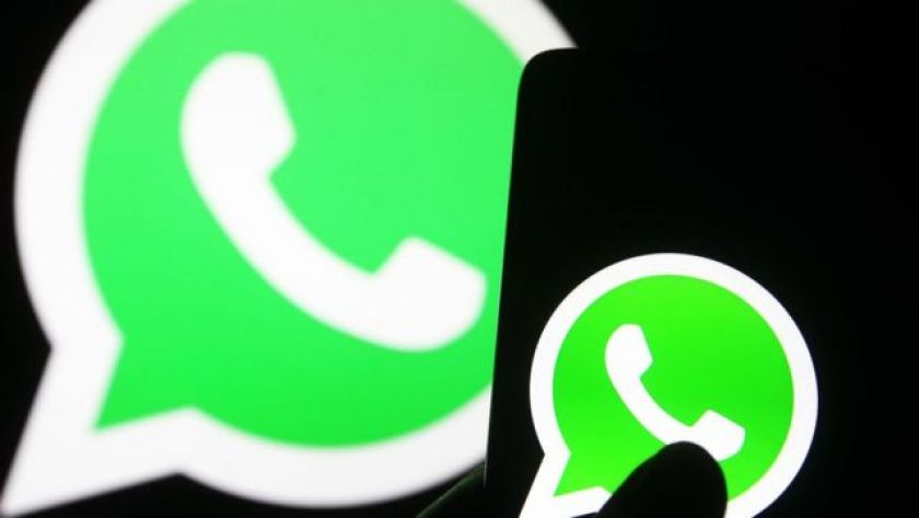 WhatsApp logo on mobile screen and projected on larger screen at the back