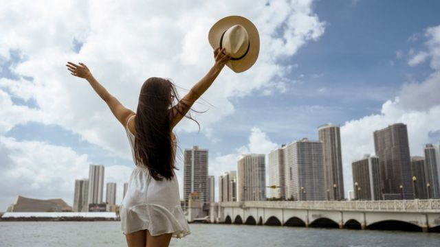 woman raises her hat in Miami