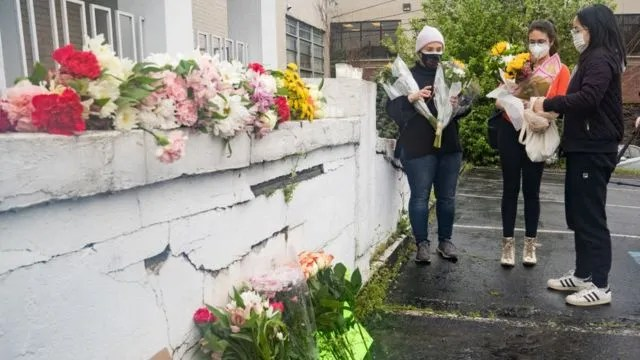 추모객들이 총격 사건이 벌어진 애틀랜타 '영스 아시안 마사지' 앞에 꽃을 놓고 있다