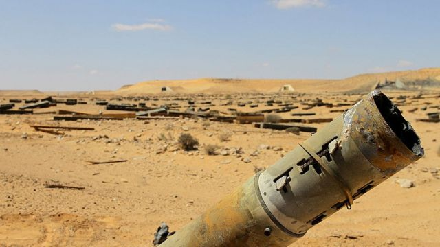A rocket sticks out in the desert as thousands more weapons are scattered in the distance abandoned by Gaddafi's forces in the desert near Jufra - 2011