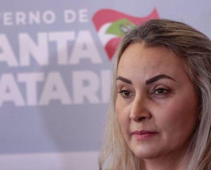 Daniela aparece de perfil, com painel atrás dizendo 'Governo de Santa Catarina'