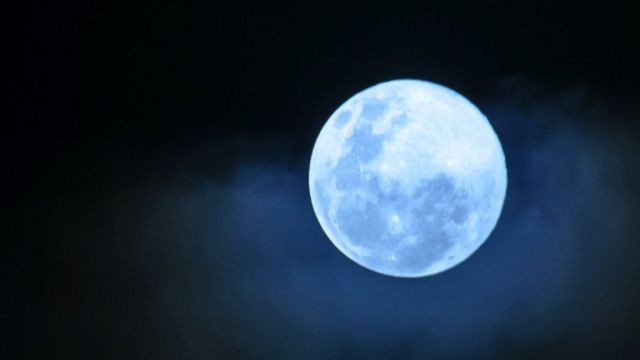 Close up of a full moon with a blue tinge