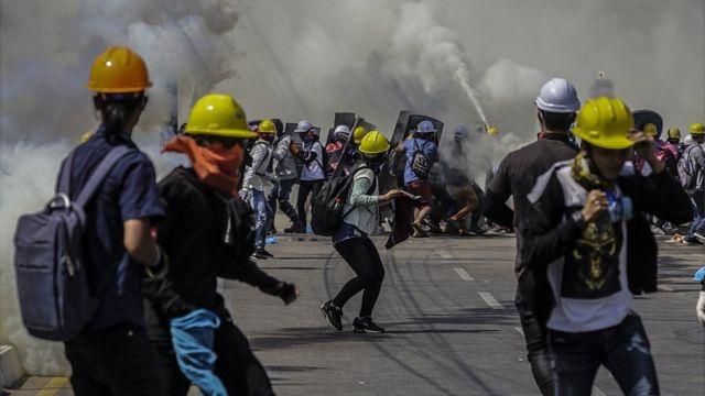 La policía disparando gas lacrimógeno contra unos manifestantes que protestan en Rangún contra el golpe militar.