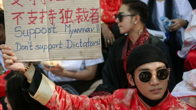 Paing Takhon holding up a sign