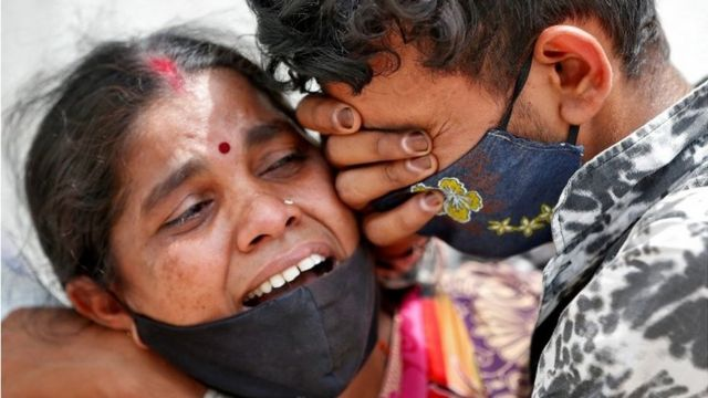 A woman mourns with her son after her husband died due to the coronavirus disease (COVID-19) outside a mortuary of a COVID-19 hospital in Ahmedabad, India, April 20, 2021