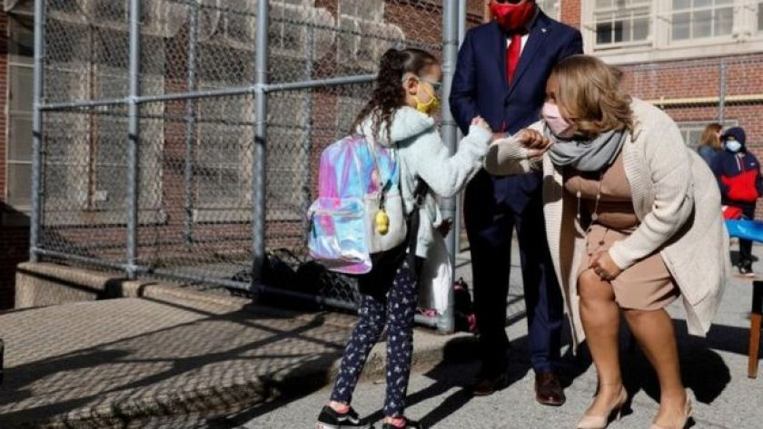 Teacher greets student at school in New York, in April photo
