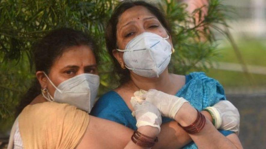인도 뉴델리의 한 병원 앞에서 코로나19로 가족을 잃은 가족들이 슬픔에 잠겨있다